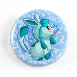 A cute chibi drawing by Camie M. Anderson of Glaceon from Pokemon on a handmade button