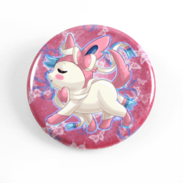 A cute chibi drawing by Camie M. Anderson of Sylveon from Pokemon on a handmade button