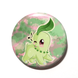 A cute chibi version of Chikorita from Pokemon drawn by Camie M. Anderson on a handmade button.