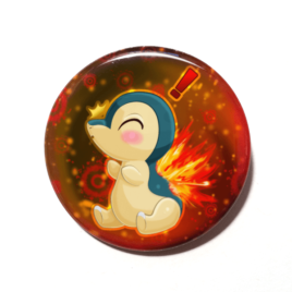 A cute chibi version of Cyndaquil from Pokemon drawn by Camie M. Anderson on a handmade button.