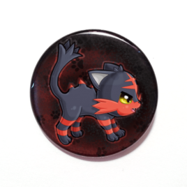 A cute chibi version of Litten from Pokemon drawn by Camie M. Anderson on a handmade button