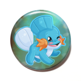 A cute chibi version of Mudkip from Pokemon drawn by Camie M. Anderson on a handmade button