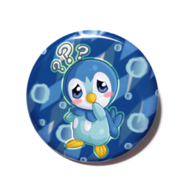 A cute chibi version of Piplup from Pokemon drawn by Camie M. Anderson on a handmade button