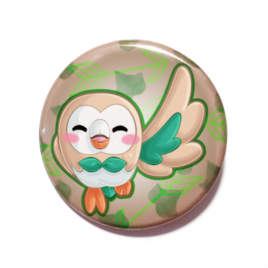 A cute chibi drawing of Rowlet from Pokemon on a handmade button by Camie M. Anderson