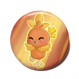 A cute chibi version of Torchic from Pokemon drawn by Camie M. Anderson on a handmade button