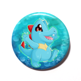 A cute chibi version of Totodile from Pokemon drawn by Camie M. Anderson on a handmade button.