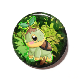 A cute chibi version of Turtwig from POkemon drawn by Camie M. Anderson on a handmade button